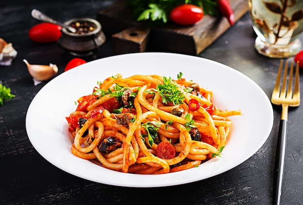 Spaghetti alla puttanesca - piatto di pasta italiana con pomodori, olive nere, capperi, acciughe e prezzemolo.