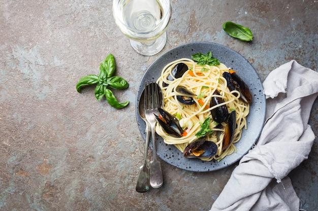 Spaghetti allo scoglio, pasta con frutti di mare, cozze su un piatto di ceramica grigia su pietra
