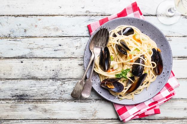 Spaghetti allo scoglio, pasta con frutti di mare, cozze su un piatto di ceramica grigia su legno