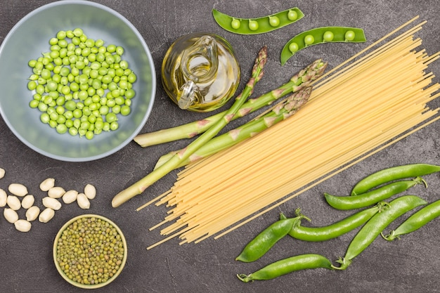 Spaghetti, asparagi e baccelli di piselli sul tavolo. piselli verdi e semole di fagioli verdi in ciotole. sfondo nero. lay piatto