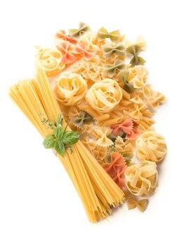 Spaghetti e basilico isolati su priorità bassa bianca.