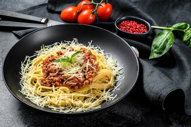 Spaghetti alla bolognese con pomodoro e carne macinata, parmigiano e basilico. sfondo nero. vista dall'alto