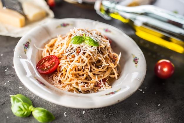 Spaghetti alla bolognese con ingredienti basilico pomodoro parmigiano e olio d'oliva.