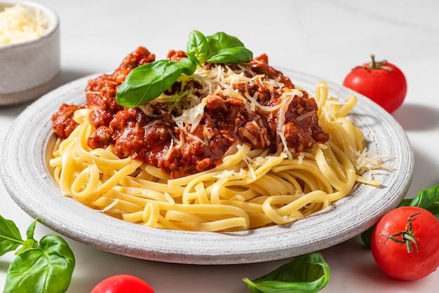 Spaghetti alla bolognese con salsa di carne macinata, pomodori, parmigiano e basilico fresco in un piatto sul tavolo bianco