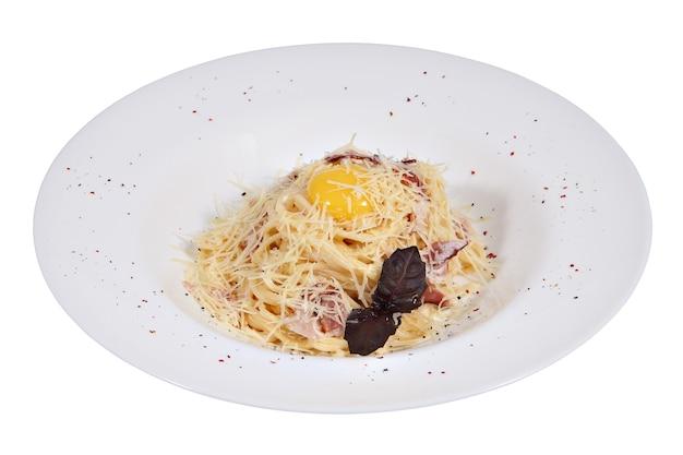 Spaghetti alla carbonara con pancetta fritta e formaggio condita con tuorlo su un piatto bianco isolato su sfondo bianco.