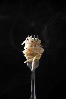 Spaghetti sulla forcella con vapore su sfondo scuro