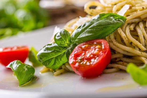 Spaghetti. spaghetti di pasta italiana con pomodorini pesto di basilico e olio d'oliva.