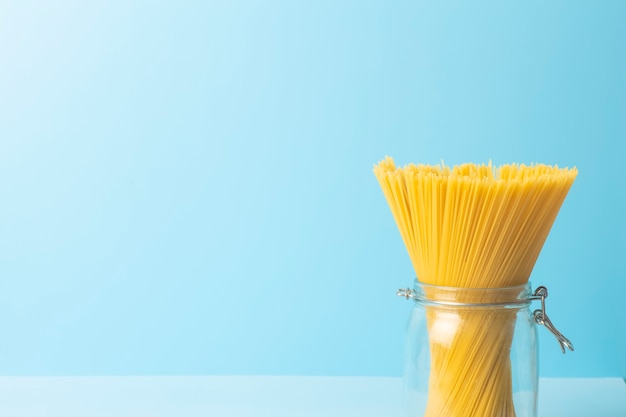Pasta degli spaghetti su una priorità bassa blu in bianco. spaghetti isolati freschi crudi in un barattolo prima di preparare il cibo italiano.