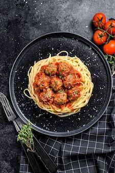 Spaghetti con polpette di carne e salsa di pomodoro. cucina italiana. sfondo nero. vista dall'alto.