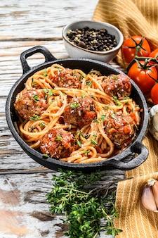 Spaghetti con polpette di carne e salsa di pomodoro. fondo in legno bianco. vista dall'alto.