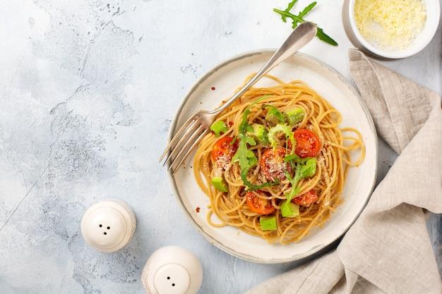 Spaghetti con pesto, avocado e pomodori in piatto bianco rustico. concetto di cibo vegano crudo. vista dall'alto.