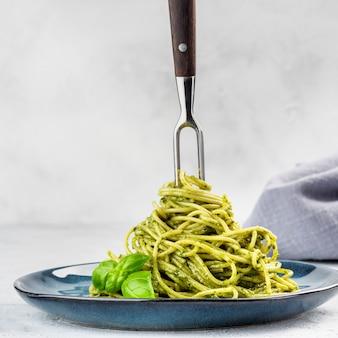 Spaghetti al pesto su un piatto blu e con una forchetta per torsione nel mezzo