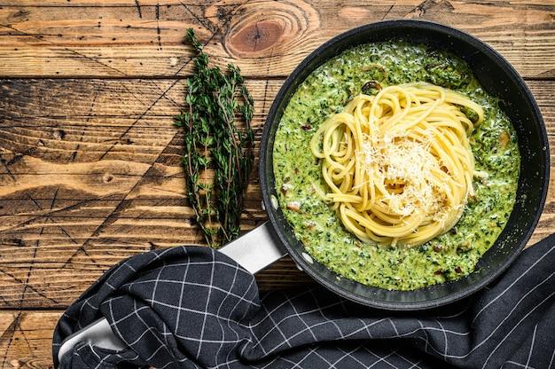 Spaghetti agli spinaci in salsa di panna con parmigiano in padella. fondo in legno. vista dall'alto. copia spazio.