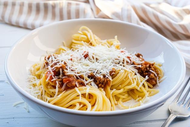 Spaghetti al sugo di carne di pomodoro e formaggio in un piatto bianco.