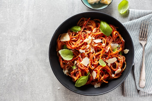 Pasta degli spaghetti con formaggio salsa di pomodoro e basilico servito in una ciotola su grigio.