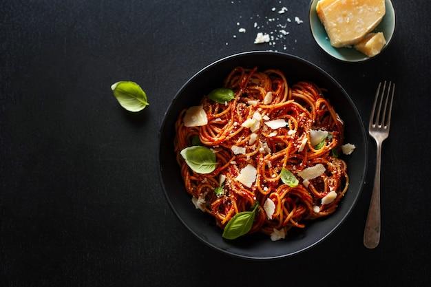 Pasta degli spaghetti con formaggio salsa di pomodoro e basilico servito in una ciotola.