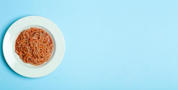 Pasta degli spaghetti con salsa di pomodoro su una zolla bianca su una priorità bassa vuota blu. sfondo di piatto di pasta italiana.