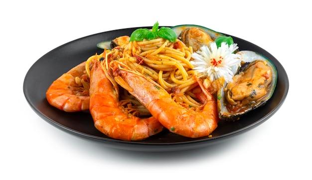 Spaghetti ai frutti di mare ragù alla bolognese fatti in casa cibo italiano stile fusion decorazione con basilico dolce e porro intagliato a forma di fiore vista laterale