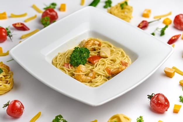 Spaghetti ai frutti di mare pasta con gamberi gamberetti e pomodori vista dall'alto su sfondo bianco