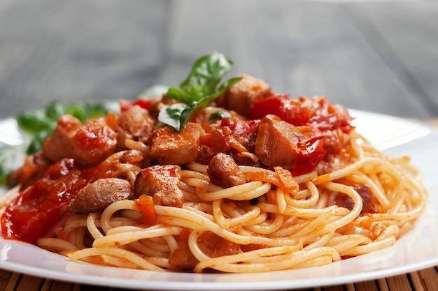 Spaghetti al pomodoro con pollo, pomodori, decorati con prezzemolo su un tavolo di legno