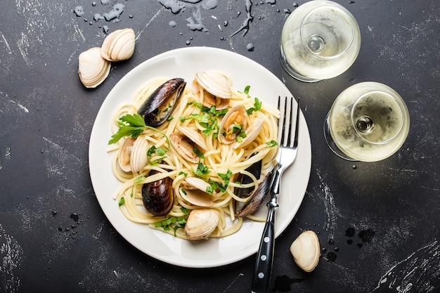 Spaghetti vongole, pasta di pesce italiano con vongole e cozze, nel piatto con erbe aromatiche e due bicchieri di vino bianco su fondo di pietra rustico.