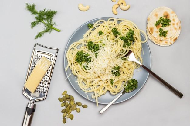 Spaghetti con pasta di broccoli e forchetta e cucchiaio su piatto in ceramica