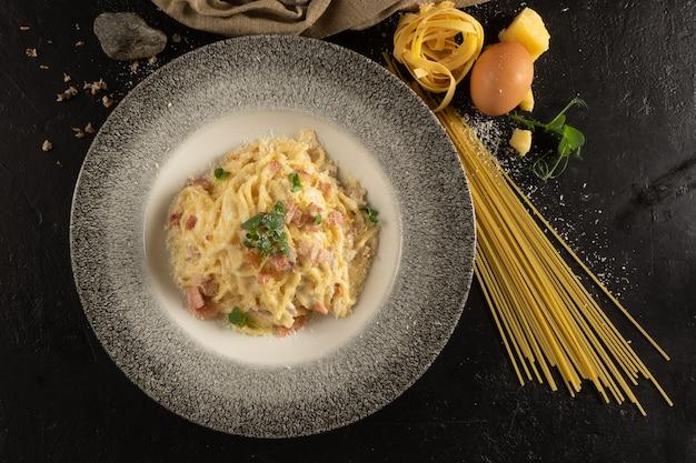 Spaghetti con formaggio e pancetta. un piatto di pasta calda, uova, formaggio ed erbe aromatiche su un tavolo da cucina in pietra nera