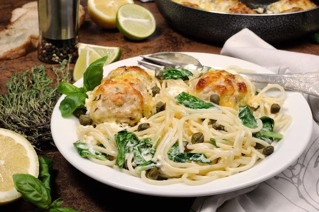Spaghetti con polpette di pollo in salsa di crema di formaggio, spinaci e capperi