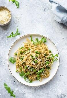 Spaghetti con avocado di piselli in un piatto su fondo di marmo chiaro