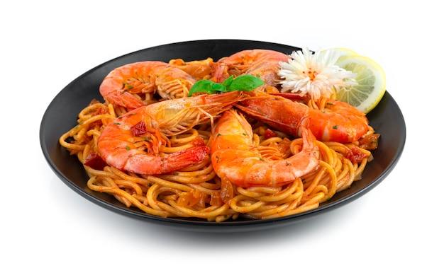 Spaghetti con ragù di gamberi alla bolognese cucina italiana fatta in casa in stile fusion decorazione con basilico dolce e veduta laterale a forma di fiore di porro intagliato
