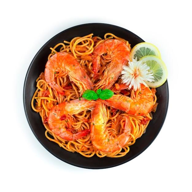 Spaghetti con ragù di gamberi alla bolognese cucina italiana fatta in casa stile fusion decorazione con basilico dolce e scolpito a forma di fiore di porro vista dall'alto