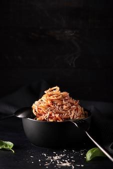 Spaghetti con salsa di pomodoro e parmigiano in ciotola nera