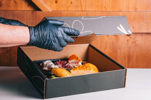 Set da colazione spagnola per consegna omelette con patate panino al prosciutto iberico in una scatola di cartone consegna sicura