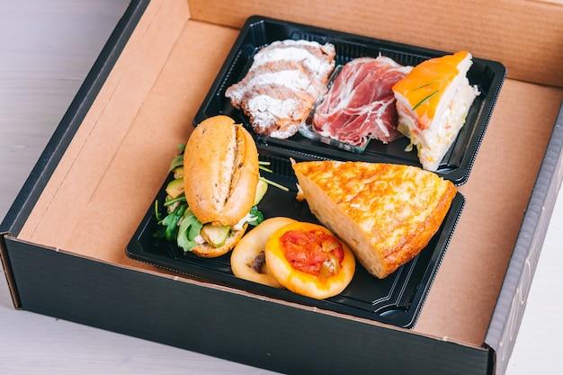 Set da colazione spagnola per consegna omelette con patate panino al prosciutto iberico in una scatola di cartone