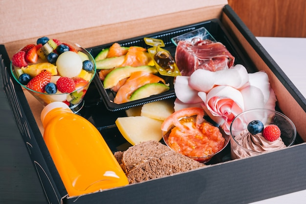 Set colazione spagnola con consegna salmone, prosciutto iberico, succo d'arancia formaggio in una scatola di cartone consegna sicura