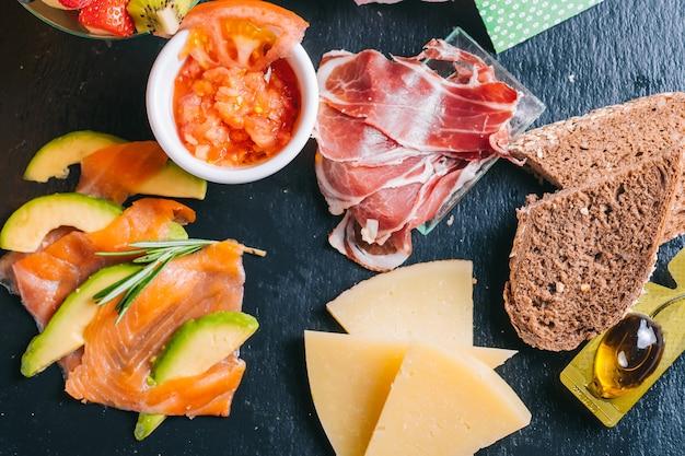 Set colazione spagnola con consegna salmone e prosciutto iberico, formaggio, pomodori con fette di pane nero in lamiera nera