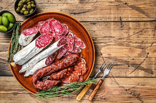 Salumi spagnoli con salsicce affettate salame, fuet e chorizo su un piatto rustico. fondo in legno. vista dall'alto. copia spazio.