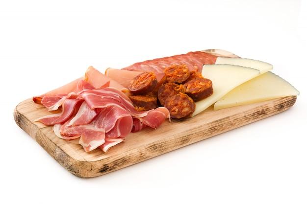 Embutidos spagnoli dei salumi formaggio, salsiccia e prosciutto su bianco