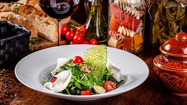Cucina spagnola. insalata mista di pesce, spinaci, uova di quaglia, sgombro in scatola, olive, condita con olio d'oliva, sesamo e chips di riso