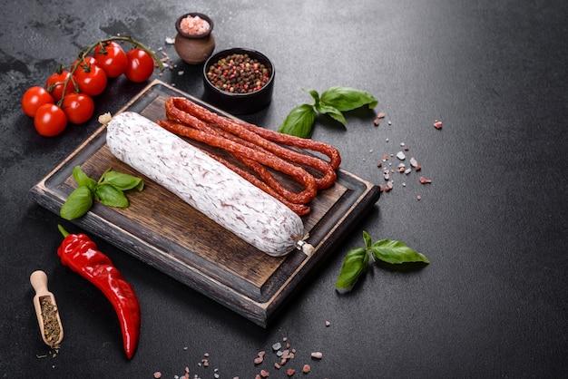 Salame di salsiccia secca spagnola su fondo di cemento scuro. preparazione di buonissimi panini freschi