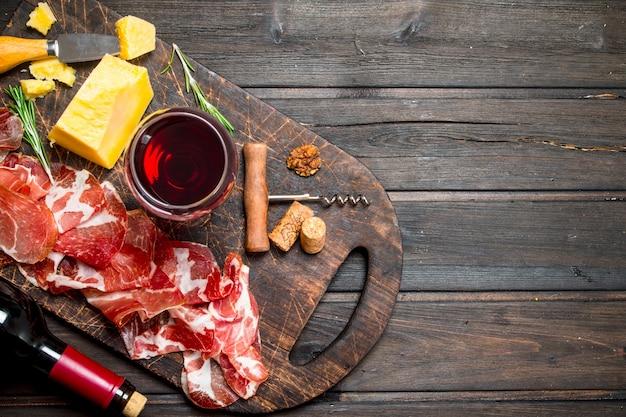Prosciutto spagnolo con un bicchiere di vino rosso. su uno sfondo di legno.