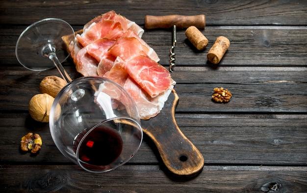 Prosciutto spagnolo con vino rosso e noci. su uno sfondo di legno.