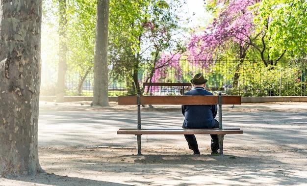 Lo spagnolo vecchio seduto rilassante su una panchina nel parco del retiro a madrid, spagna - messa a fuoco selettiva.