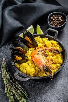 La paella spagnola ai frutti di mare, gamberi, gamberetti, cozze. sfondo nero. vista dall'alto.