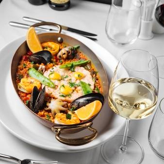 Paella spagnola di pesce in padella con un bicchiere di vino