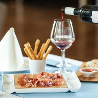 Jamon spagnolo di maiale a fette con vino rosso sul tavolo del ristorante