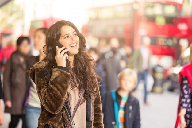 Donna spagnola parlando al telefono con persone sfocate