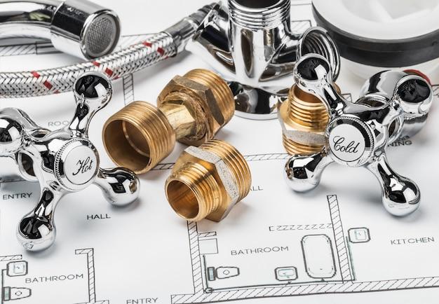 Pezzi di ricambio e strumenti distesi sul disegno per l'impianto idraulico di riparazione