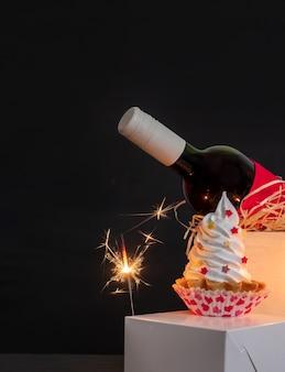 Sparkler, bottiglia di vino e torta di meringa sullo sfondo nero per san valentino.