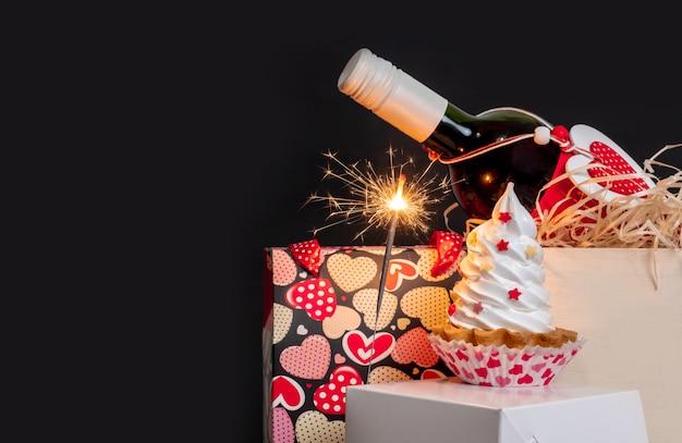 Sparkler, bottiglia di vino, shopping bag con cuori e torta di meringa su sfondo nero per san valentino.